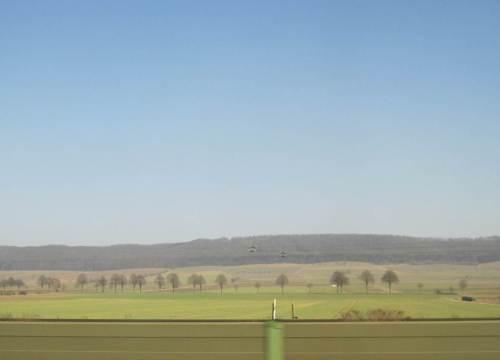 Schnell eilt der Zug hinter Lärmschutzwänden vorbei an unsäglich ausgeräumter Subventions-Agrarindustrie-Landschaft.