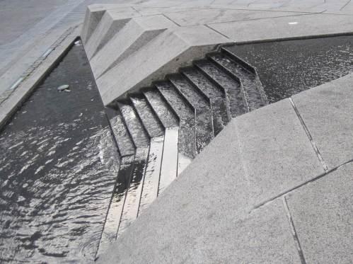 Mein erster Rundgang in Aalborg findet statt bei kühlem Sonnenschein und Starkwind. Sogar das Wasser auf diesem Stadtbrunnen kräuselt sich windbewegt.