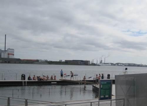 Am Südufer des Limfjord ist eine öffentliche Badeanstalt. Hier hat gerade nach langem Stupsen und Klopfen ein Schüler seine Kontrahentin aus dem Gleichgewicht gebracht. - Im Hintergrund Aalborgs Industrie.