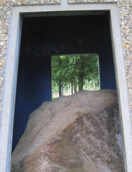 """Aufwärts geht es durch den Skulpturenpark, hier: Blick über einen Eiszeitstein (""""Findling"""") auf Waldlandschaft."""