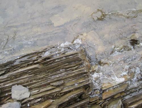 von Wellen umspülte senkrecht stehende messerscharfe Steinformation