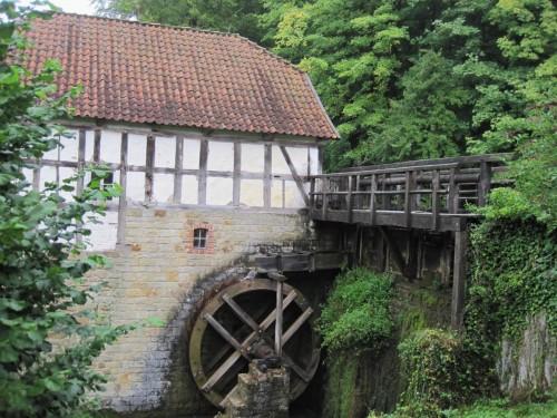 """Nahe beim Freilichtmuseumseingang die dörfliche Wassermühle mit hohem Bacheinstau, das Rad """"oberschlächtig"""" mit Wasser beschickt."""