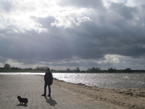 Wieder an der Anlegerlandzunge - Frau und Hund werfen harte Schatten beim Sonnendurchbruch.