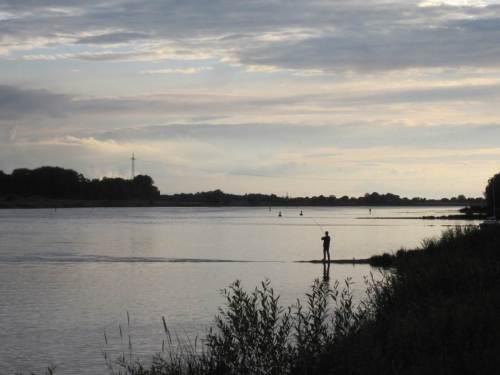 Das fängt ja gut an, Lauenburger Elbe-Abend mit Angler auf einer Buhne. Die Rute ist krumm.