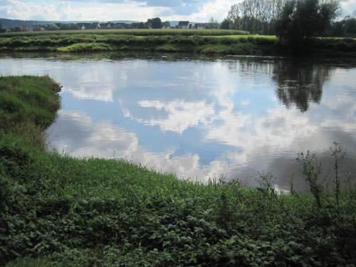 Der Himmel spiegelt sich auf klarem Weserwasser im Buhnenfeld.