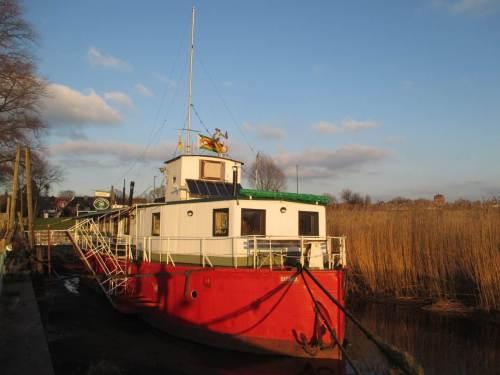 Abendsonne beleuchtet das Theaterschiff Batavia, bei Tideniedrigwasser auf Elbschlick aufliegend.