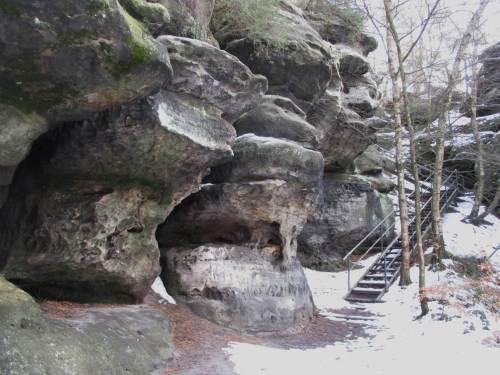 Beschneite Treppen neben imposanter Sandsteinkulisse.