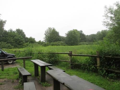 Parkplatz und Rastbereich, nebendran eine halboffene Hütte - gut bei jedem Wetter, besonders bei Dauerregen.