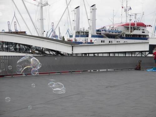 Die Seifenblasen erfreuen auch die Passanten, hoch oben auf der Hochwasserschutzanlage.