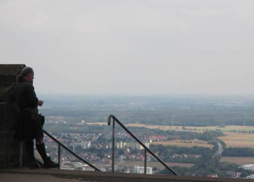 So ganz allein sind wir nicht - da lehnt ein Schottischer Dudelsackpfeifer am Mauerwerk und blickt über die Weseraue.