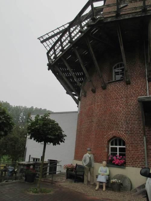 Herr und Frau Müller vor ihrer Doppelmühle, Wasser- und Windmühle an einem Standort.