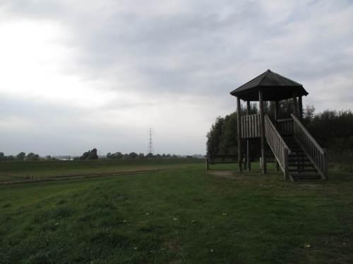 Auf einem künstlichen Hügel überblickt ein kleiner Turm die Landschaft.
