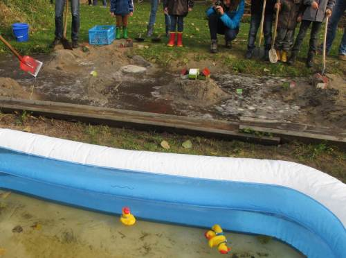 Den Besuchern wird mehr geboten. Aus einem aufgestauten Teich kann gezielt Wasser in einen modellartigen Talraum geleitet werden. - Oje, da stehen ja Häuser.