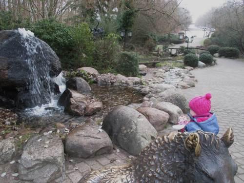 """Am Eingang begeistern Groß und Klein eine Wildschwein-Skulptur, die schon ordentlich """"golden"""" gerubbelt ist und ein künstlicher Quellwasserfall mit Bachlauf."""