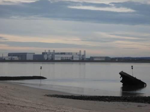 Blick über ein Schiffswrack und das als Elbe-Lunge nicht mehr funktionierende Mühlenberger Loch auf die aufgespülte Airbus-Ansiedlung.
