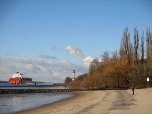 Schnell passiert der Containerfrachter den Anleger Wittenbergen. Weiss leuchtet der Wasserdampf vom KoKW Wedel.