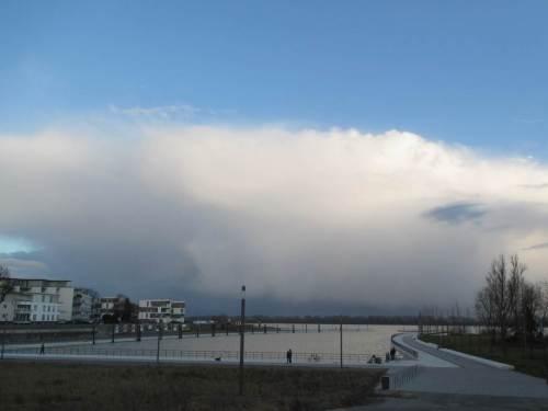 Am Schulauer Hafen angekommen - Tidehochwasser plus X. Jenseits der Elbe, in Niedersachsen rast offenbar ein größerer Graupelschauer durch. Wie gut, dass ich am Nordufer unter blauem Himmel stehe.